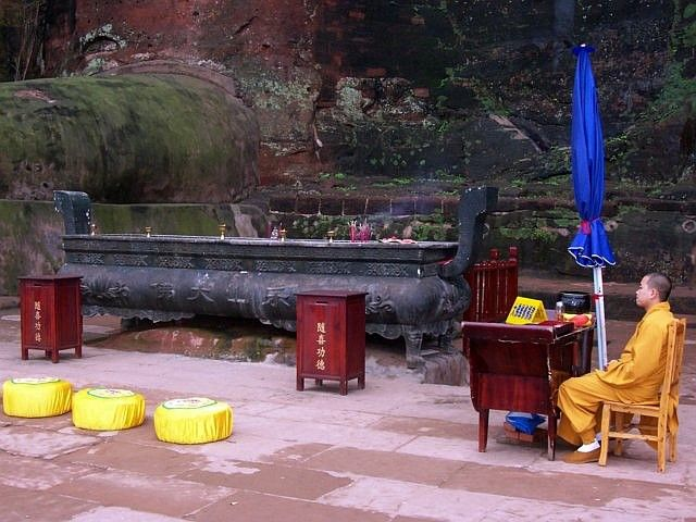 Leshan Buddhist site - Monk and altar at the foot of the Great Buddha