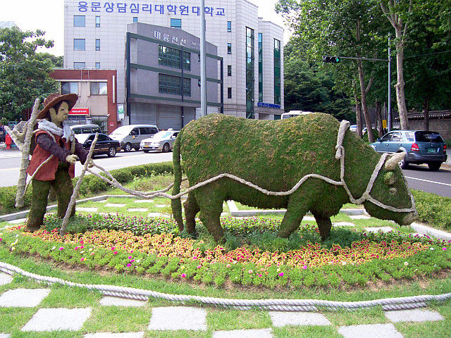 Central Seoul - Sculptures of an ox and a farmer made with earth and moss